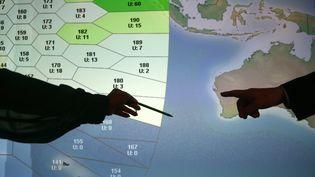 Des employés du groupe britannique Inmarsat montrent la zone où le Boeing disparu est soupçonné d'avoir fini sa course, le 25 mars 2014. (ANDREW WINNING / REUTERS)