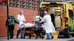Des soignants prennent en charge un patient atteint du Covid-19 devant les urgences du Royal London Hospital, à Londres (Royaume-Uni), le 19 janvier 2021. (DAVID CLIFF / NURPHOTO / AFP)