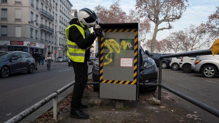 Un homme tente de détruire un radar, à Lyon le 19 janvier 2019. (ROMAIN LAFABREGUE / AFP)