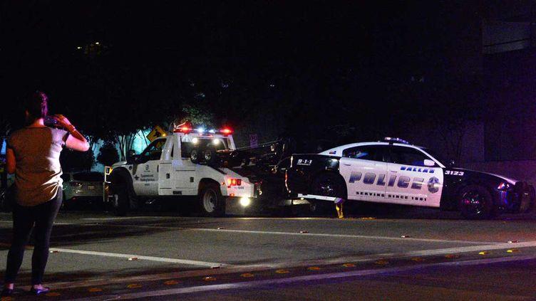 (La voiture de policiers pris pour cible, évacuée à Dallas, vendredi. © MaxPPP)