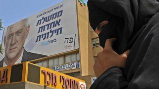 Une femme bédouine marche près d'une affiche électorale montrant le candidat Benny Gantz, le 15 septembre 2019 à Beer-Sheva (sud d'Israël). (HAZEM BADER / AFP)