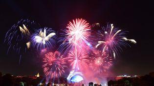 Le feu d'artifice du 14-Juillet à Paris, tiré derrière la tour Eiffel. (MUSTAFA YALCIN / AFP)