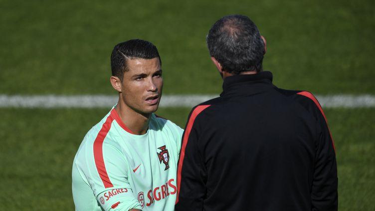 Le sélectionneur du Portugal Fernando Santos en discussion à l'entraînement avec Cristiano Ronaldo (FRANCISCO LEONG / AFP)