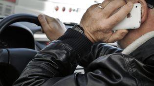 Une personne téléphone au volant de sa voiture le 4 janvier 2012 à Lyon. (JEAN-PHILIPPE KSIAZEK / AFP)