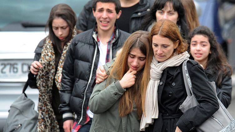Des parents consolent leurs enfants après une fusillade dans une école juive de Toulouse (Haute-Garonne), le 19 mars 2012. (REMY GABALDA / AFP)