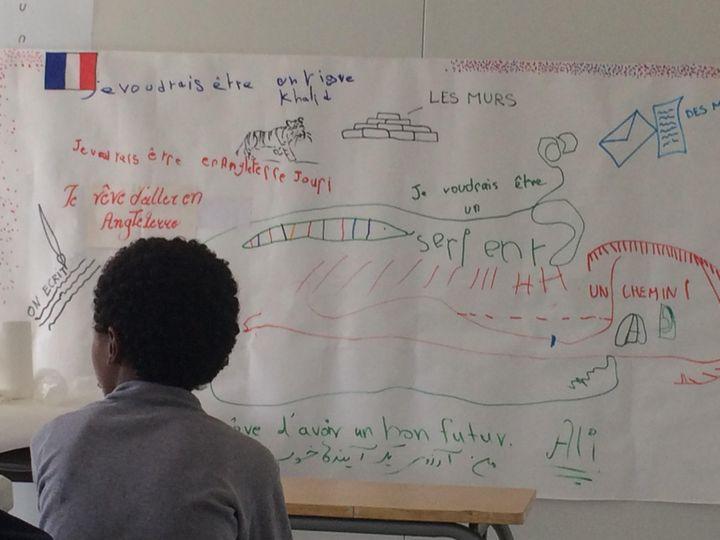 """Un enfant de la """"jungle"""" de Calais, devant les messages laissés par les élèves. (KOCILA MAKDECHE / FRANCEINFO)"""