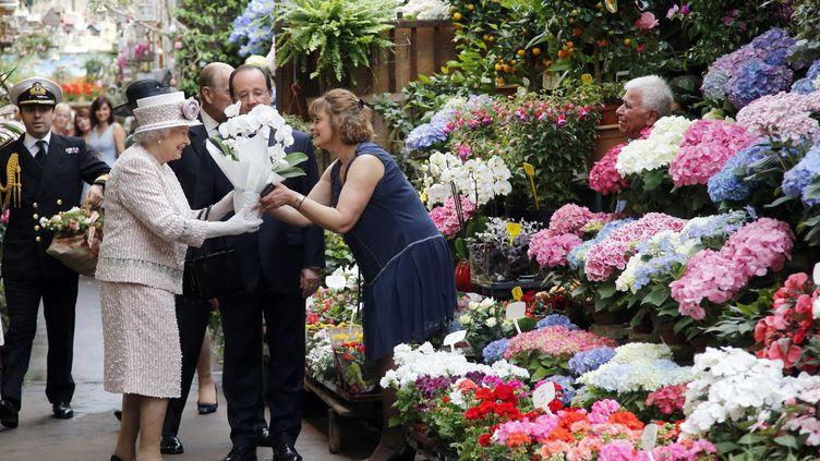 Elizabeth II se voit offrir des fleurs au marché de l'île Saint-Louis, à Paris, le 7 juin 2014. (FRANCOIS MORI / POOL / AFP)