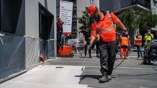 Unepeinture anti-chaleur est déposée afin de lutter contre la chaleur au sol sur les trottoirs de la métropole de Lyon, le 7 juillet 2021. (NICOLAS LIPONNE / HANS LUCAS / AFP)