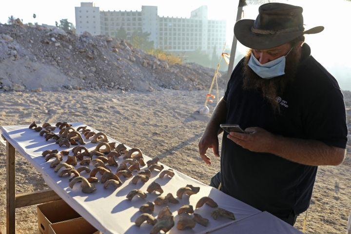 Benjamin Storchan, directeur des fouilles à l'Autorité israélienne des Antiquités (AIA), devant les fragments gravés de sceaux retrouvés à Jérusalem. (MENAHEM KAHANA / AFP)