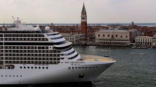 Un bâteau de croisière quitte Venise, en passant à côté de la Bell Tower et le palais des Doges, le 5 juin 2021. Les grands navires de ce type ne pourront plus entrer dans le centre de la ville à partir du 1er août 2021. (MIGUEL MEDINA / AFP)