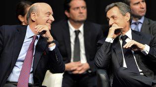 Alain Juppé et Nicolas Sarkozy, le 14 octobre 2015, à Limoges (Haute-Vienne), lors d'un meeting pour les régionales. (NICOLAS TUCAT / AFP)