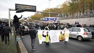"""Des manifestants bloquent brièvement le périphérique parisien, au niveau de la Porte de Champerret, à l'occasion des un an des """"gilets jaunes"""", le 16 novembre 2019. (MARTIN BUREAU / AFP)"""