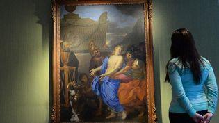 """Une employée de la maison Christie's admire le tableau """"Le sacrifice de Polyxène"""" de Charles Le Brun, en janvier 2013  (Emmanuel Dunand/AFP)"""
