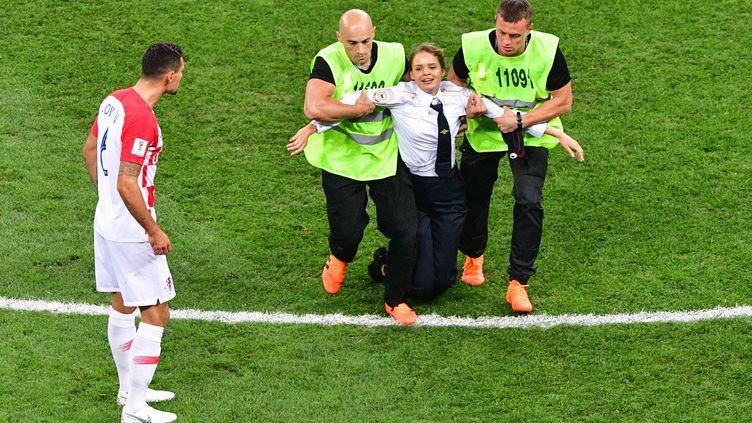 Une membre du groupe Pussy Riot est arrêtée après avoir interrompu la finale de la Coupe du monde entre la France et la Croatie, dimanche 15 juillet 2018 à Moscou. (MLADEN ANTONOV / AFP)