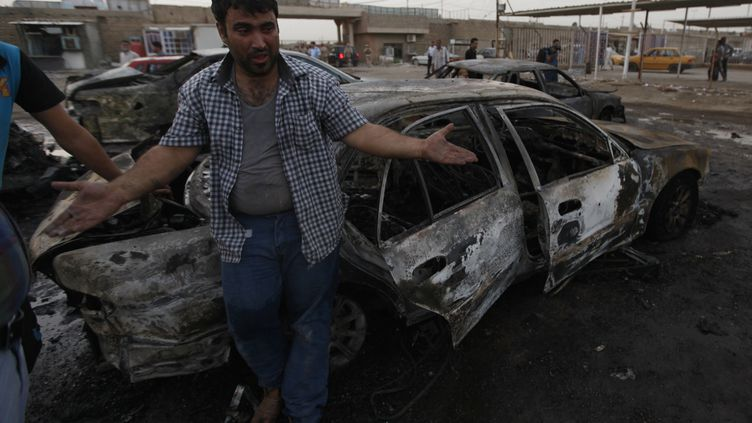 Un homme constate les dégâts après un attentat à la voiture piégée perpétré lundi 27 mai 2013 à Bagdad (Irak). (THAIER AL-SUDANI / REUTERS)