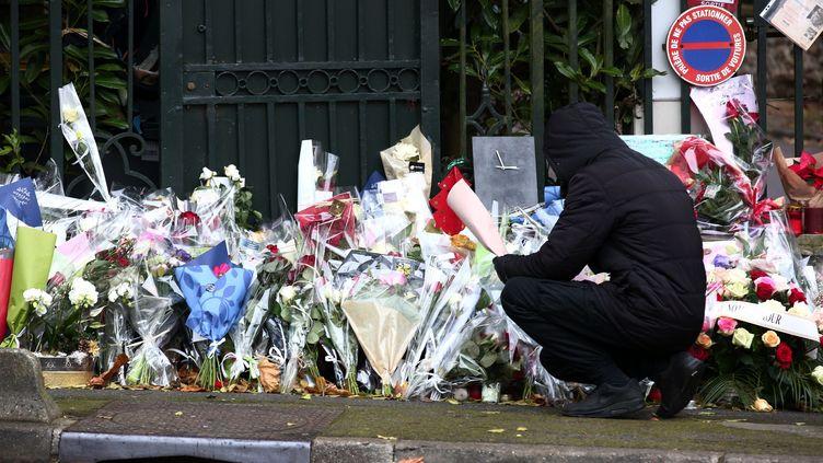 Un homme dépose des fleurs devant la propriété de Johnny Hallyday, à Marnes-la-Coquette (Hauts-de-Seine), après la mort du chanteur, le 7 décembre 2017. (MAXPPP)