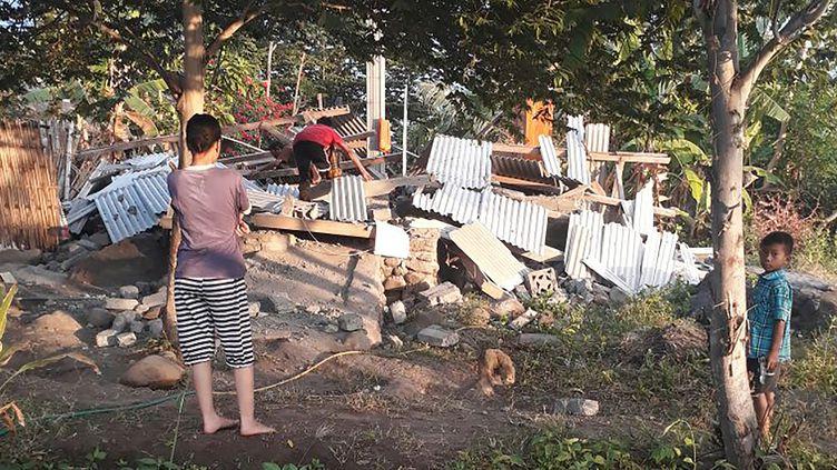 Des indonésiens face à des décombres à la suite d'un séisme demagnitude 6,4 sur l'île de Lombok, le 29 juillet 2018. (NUSA TENGGARA BARAT DISASTER MIT / AFP)