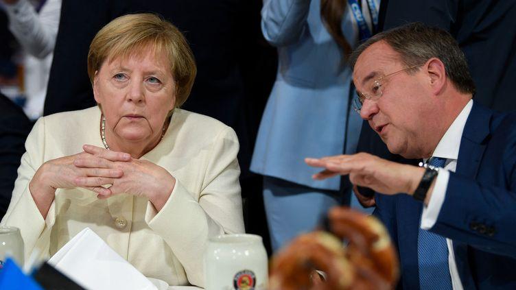 La chancelière allemande Angela Merkel (à gauche) est assise à côté du leader du parti de l'Union chrétienne-démocrate (CDU) et candidat à la chancellerie Armin Laschet lors du dernier rassemblement de l'Union chrétienne-démocrate CDU à Munich, le 24 septembre 2021. (THOMAS KIENZLE / AFP)