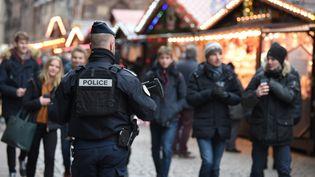 Un policier patrouille sur le marché de Noël, le 14 décembre 2018, plusieurs jours après l'attentat de Strasbourg. (PATRICK HERTZOG / AFP)