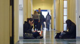Des étudiants révisent dans les couloirs de l'université Lyon-3, en 2004. (FRED DUFOUR / AFP)