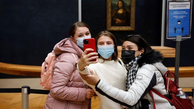 """Des adolescentes devant """"La Joconde"""" au musée du Louvre à Paris,le 14 octobre 2020. (LUDOVIC MARIN / AFP)"""