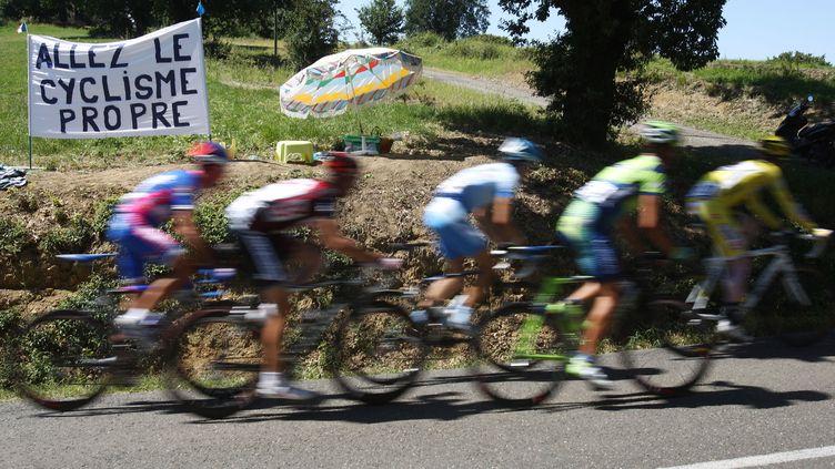 """Le peloton passe devant une banderole dénonçant le dopage cycliste et sur laquelle on peut lire """"Allez, le cyclisme propre"""" lors de la 17e étape du 94e Tour de France cycliste entre Pau et Castelsarrasin, le 26 juillet 2007. (JOEL SAGET / AFP)"""