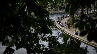 Des personnes assises et marchant le long le du canal Saint-Martin, à Paris, le 8 mai 2020. (CHRISTOPHE ARCHAMBAULT / AFP)