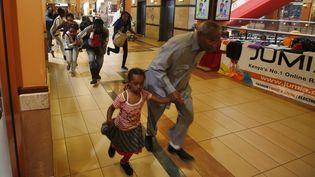 Des clients du centre commercial Westgate à Nairobi au Kenya fuient pendant l'attaque terroriste menée par des shebab somaliens le 21 septembre 2013. (GORAN TOMASEVIC / REUTERS)