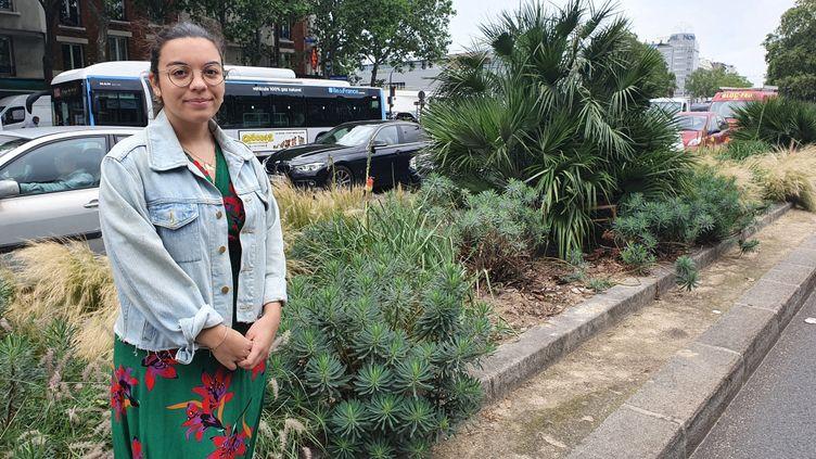 Alica Samama, chargée de mission à l'Observatoire des espèces à enjeux pour la santé humaine, devant un euphorbe, une planteirritante que l'on peut trouver en ville, comme sur ce terre-plein à Paris. (BORIS HALLIER / RADIO FRANCE)