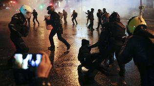 """Des policiers dispersent des manifestants, place de la République à Paris, à la fin de la mobilisation contre la proposition de loi sur la """"sécurité globale"""", le 5 décembre 2020. (GEOFFROY VAN DER HASSELT / AFP)"""