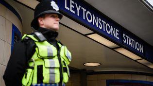 Un policier devant la station de métroLeytonstone, à Londres (Royaume-Uni), le 6 décembre 2015, au lendemain d'une attaque au couteau qui a fait 3 blessés, dont un grave. (LEON NEAL / AFP)