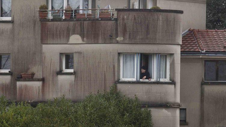 Un homme à la fenêtre d'un immeuble, à Dammartin-en-Goële, vendredi 9 janvier 2015, à bonne distance de l'endroit où sont retranchés Said et Chérif Kouachi. (GEOFFROY VAN DER HASSELT / ANADOLU AGENCY / AFP)