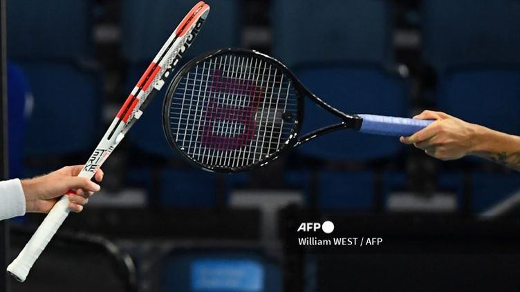 Les tennismen britanniques Cameron Norrie et Daniel Evans touchent la raquettel'un de l'autre au lieu de se serrer la main à la fin de leur match en raison du Covid-19, à l'Open d'Australie de Melbourne, le 9 février 2021. (WILLIAM WEST / AFP)
