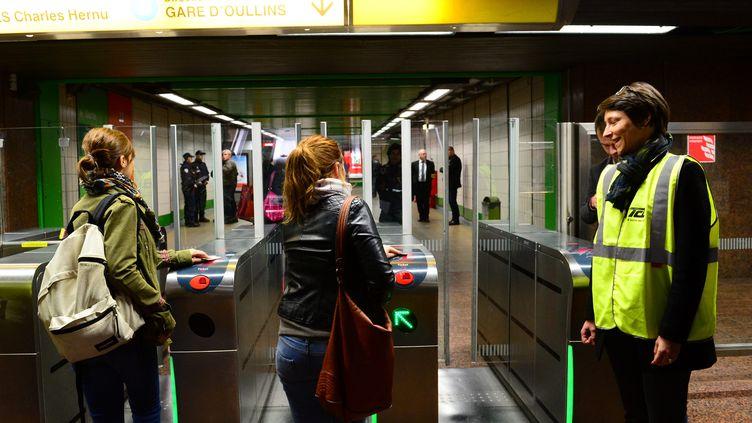 A Lyon, des contrôleurs dissuadent les usagers de frauder, à l'entrée d'une station de métro, le 3 avril 2014. (MAXPPP)