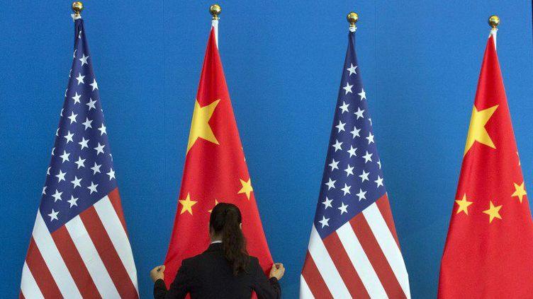 Femme ajustant les drapeaux américains et chinois en vue d'une négociation entre les deux pays.  (AFP PHOTO / POOL  NG HAN GUAN / POOL / AFP)