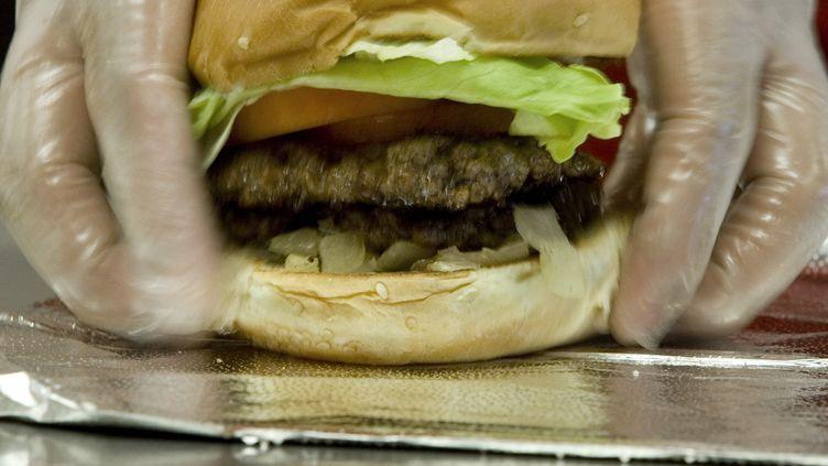 Un cheeseburger cuisiné dans un restaurant deWashington(Etats-Unis), le 25 juin 2007. (PAUL J. RICHARDS / AFP)