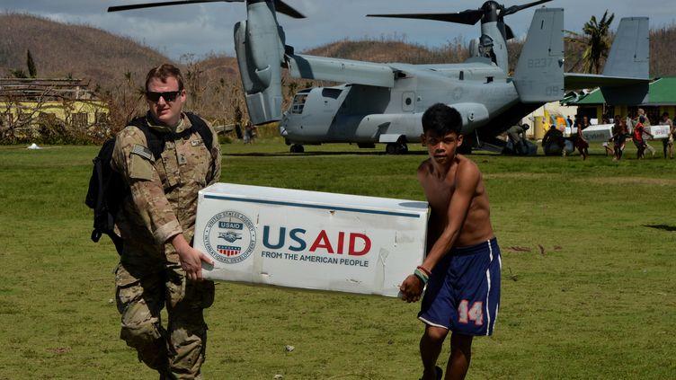 Un soldat américain aidé d'un Philippin, victime du typhon Haiyan, décharge de l'aide humanitaire à Balangiga (Philippines), le 16 novembre 2013. (MARK RALSTON / AFP)