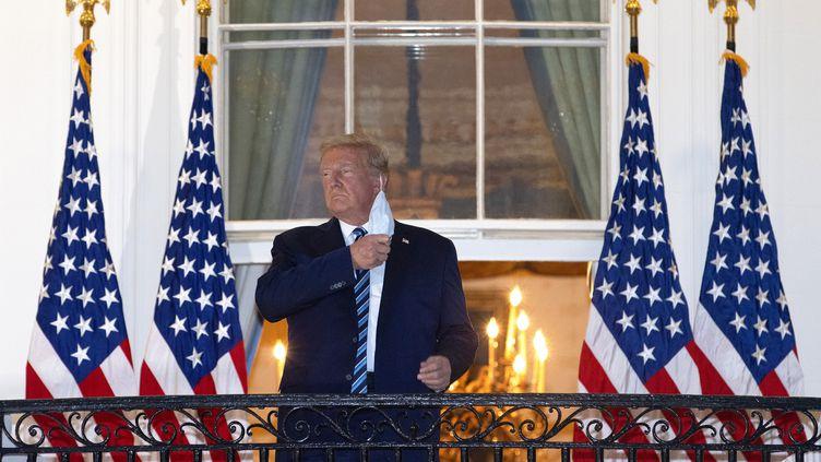 Donald Trump, de retour la Maison Blanche, enlève son masque, le 5 octobre 2020, à Washington. (WIN MCNAMEE / GETTY IMAGES NORTH AMERICA / AFP)
