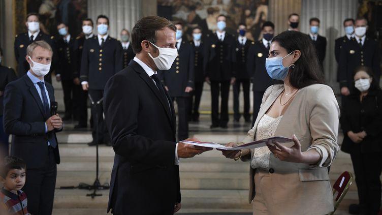 Le président Emmanuel Macron remet un livret de naturalisation à une nouvelle citoyenne française lors d'une cérémonie pour célébrer le 150e anniversaire de la proclamation de la République au Panthéon à Paris, le 4 septembre 2020. (JULIEN DE ROSA / POOL)