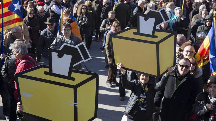 Des manifestants brandissent des pancartes en forme d'urnes électorales, le 6 février 2017 à Barcelone (Espagne), lors d'une manifestation de soutien aux anciens dirigeants de la Catalogne, jugés pour avoir organisé un référendum. (ALBERT LLOP / ANADOLU AGENCY / AFP)
