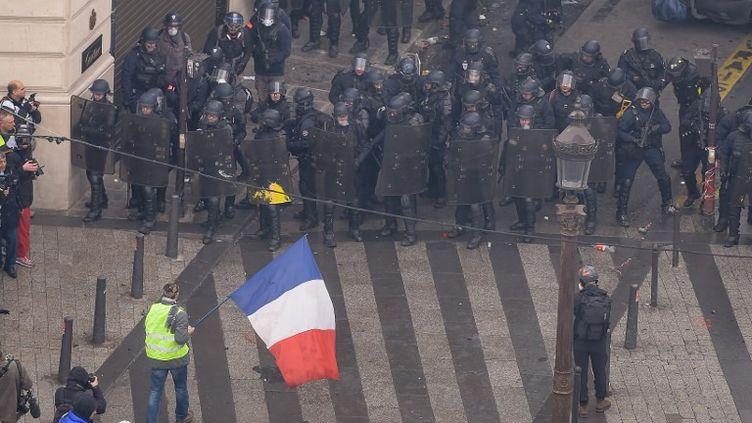 Un homme tient un drapeau tient un drapeau tricole face aux forces de l'ordre, près des Champs-Elysées à Paris, dans la matinée du 8 décembre. (LUCAS BARIOULET / AFP)