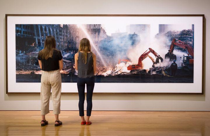Deux visiteuses observent l'une des photos de Ground Zero prises par Wim Wenders, le 10 septembre 2021 à Londres (TOLGA AKMEN / AFP)