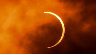 """La Lune passe devant le Soleil durant une éclipse solaire """"cercle de feu"""", au-dessus de New Delhi (Inde), le 21 juin 2020. (JEWEL SAMAD / AFP)"""