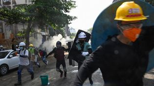 Des manifestants fuientles gaz lacrymogènes de la police anti-émeute lors d'une manifestation contre le coup d'Etat militaire, àRangoun(Birmanie), le 2 mars 2021. (STR / AFP)