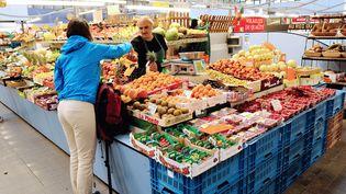 Une femme achète des fruits et légumes dans un marché, à Lille (Nord), le 18 août 2013. (PHILIPPE HUGUEN / AFP)