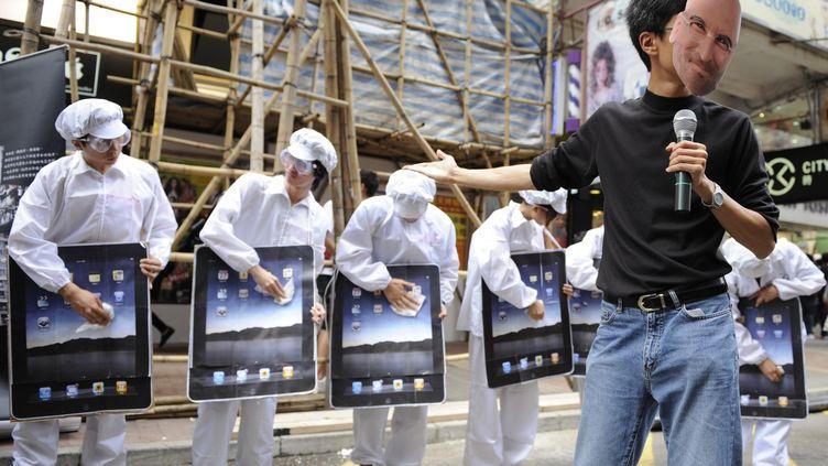 Des manifestants protestent contre les méthodes de travail en vigueur chez Foxconn, un des sous-traitants d'Apple, le 7 mai 2011 à Hong Kong. (ANTONY DICKSON / AFP)