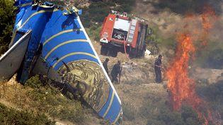 Des pompiers éteignent l'incendie provoqué par le crash d'un Boeing 737 de Helios Airways,le 14 août 2005, près d'Athènes (Grèce). (LOUISA GOULIAMAKI / AFP)