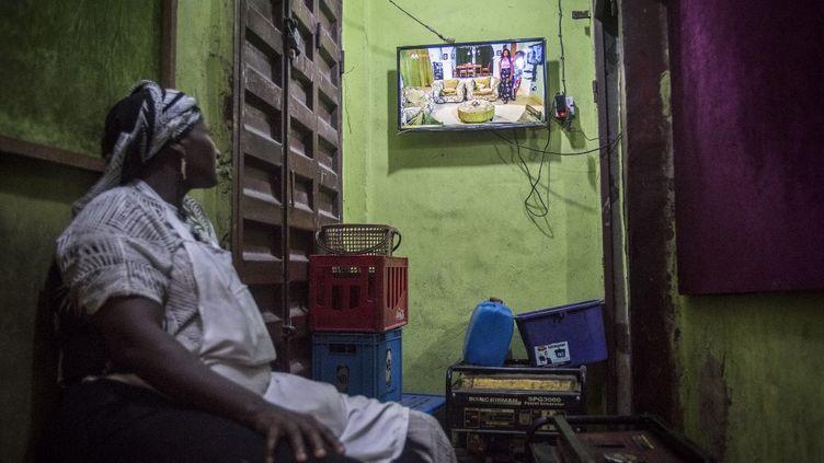 Une femme regarde un film nigérian, produit par Nollywood, dans sa boutique au marché d'Idumota à Lagos, au Nigeria, le 19 février 2019. (CRISTINA ALDEHUELA / AFP)