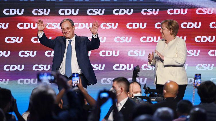 Lors d'un meeting de la CDU organisé vendredi 24 septembre à Munich, la chancelière allemande Angela Merkel (à droite) a appelé les électeurs à voter pour Armin Laschet (gauche), le candidat conservateur de son parti aux élections législatives qui auront lieu dimanche. (MATTHIAS BALK / DPA)