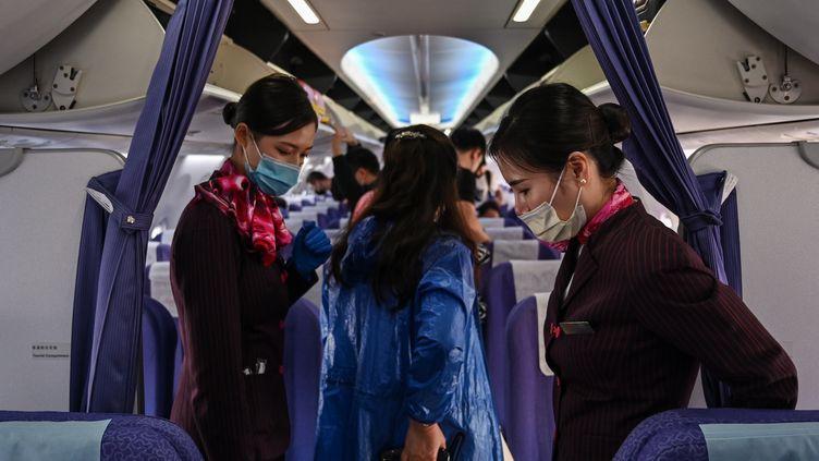 Des hôtesses de l'air portant des masques pour se protéger du coronavirus. (HECTOR RETAMAL / AFP)